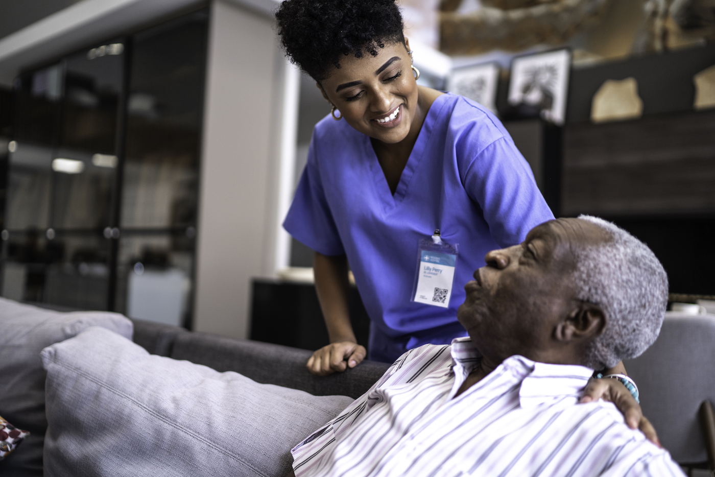 Female nurse taking care of a senior man at home